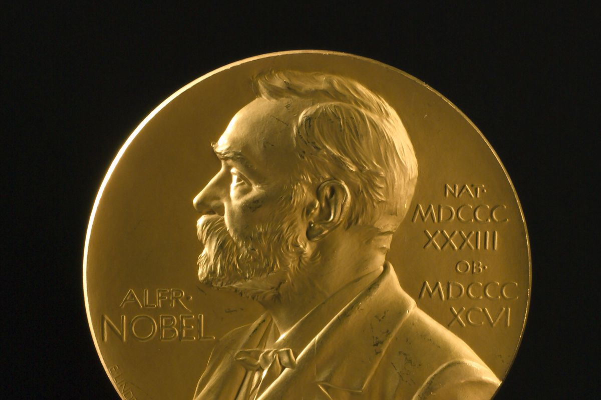 A Nobel Prize in the shape of a gold disk with a bust of Albert Nobel depicted in profile.