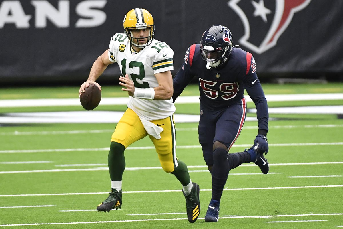 Aaron Rodgers #12 of the Green Bay Packers scrambles away from Whitney Mercilus #59 of the Houston Texans during the first quarter at NRG Stadium on October 25, 2020 in Houston, Texas.
