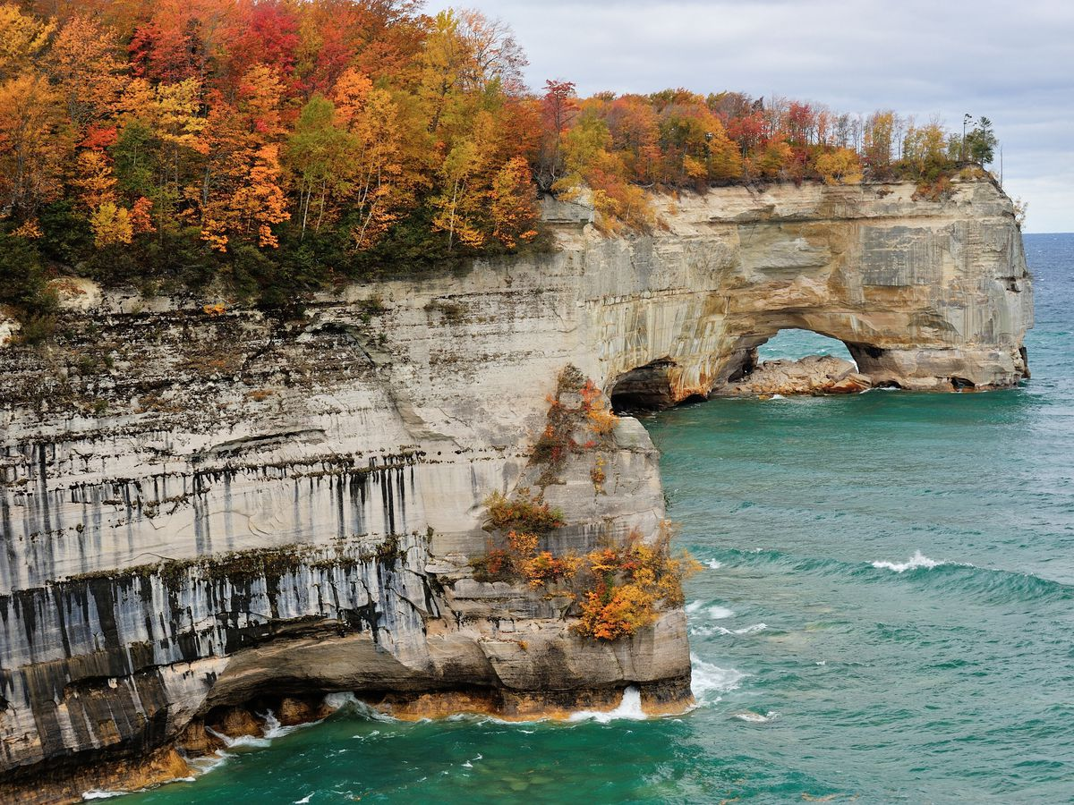 A rockface with trees that have colorful autumn leaves. The rockface is adjacent to a body of water in Michigan.