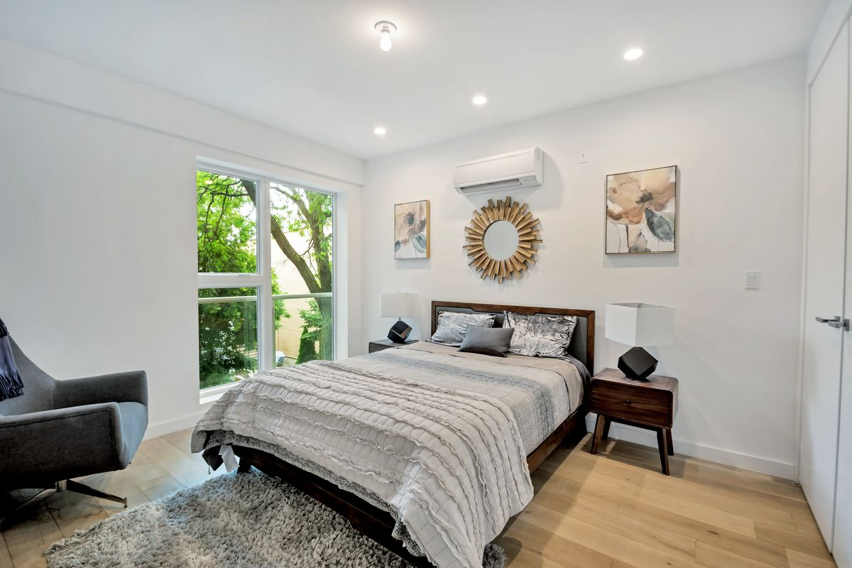 A bedroom with a small bed, hardwood floors, and a large window.