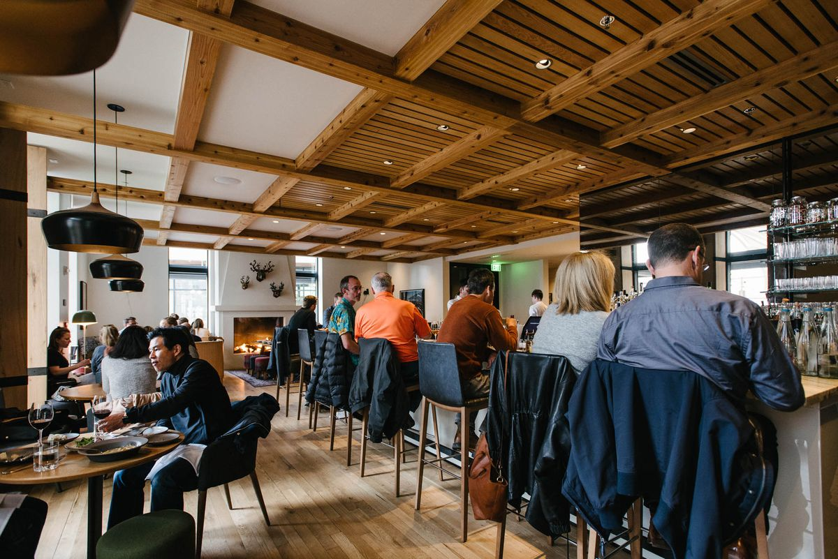 A photo of diners eating at tables and the bar at Tavernetta