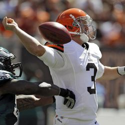 FILE - In this Sept. 9, 2012 file photo, Cleveland Browns quarterback Brandon Weeden (3) has the ball knocked from his hand by Philadelphia Eagles defensive end Trent Cole in the first quarter of an NFL football game in Cleveland. Weeden had one of the worst debuts in NFL history, a 5.1 rating. Cleveland's defense forced five turnovers, but couldn't get the one it needed to stop Michael Vick. It added up to another tough loss, but one that showed some promise for a young team.