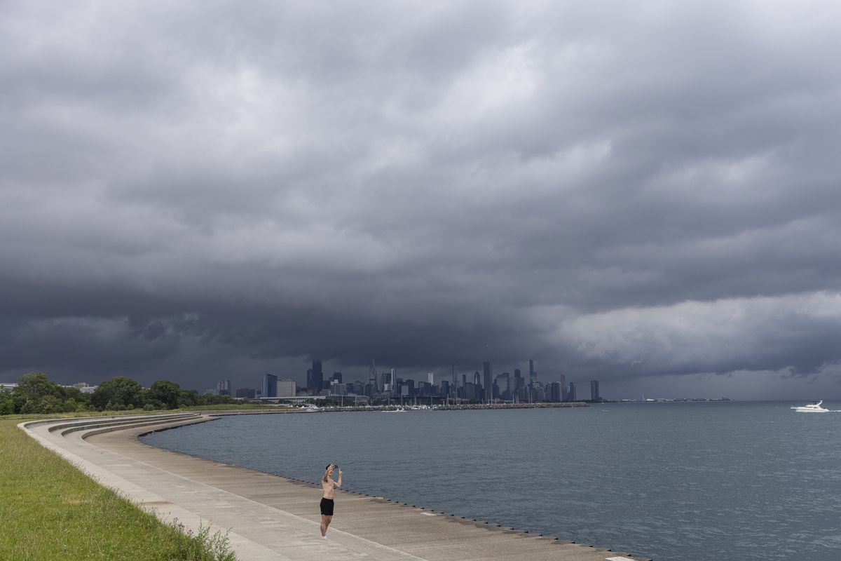 A person takes a photo of dark clouds covering portions of the downtown area Saturday afternoon.