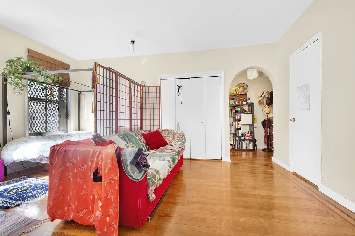 A living area with beige walls, an arched entryway, and a red couch.