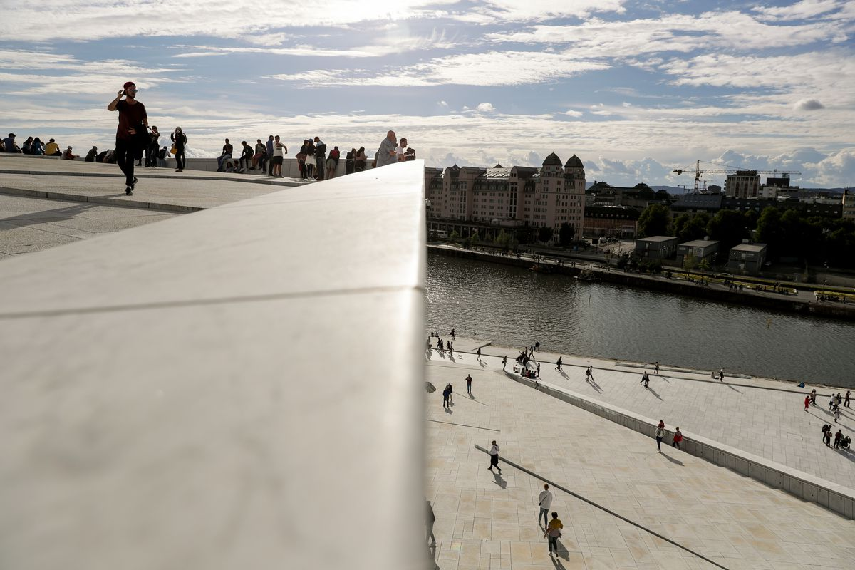 People walk around the Oslo Opera House, a popular tourist attraction, in Oslo, Norway, on Saturday, Aug. 11, 2018.