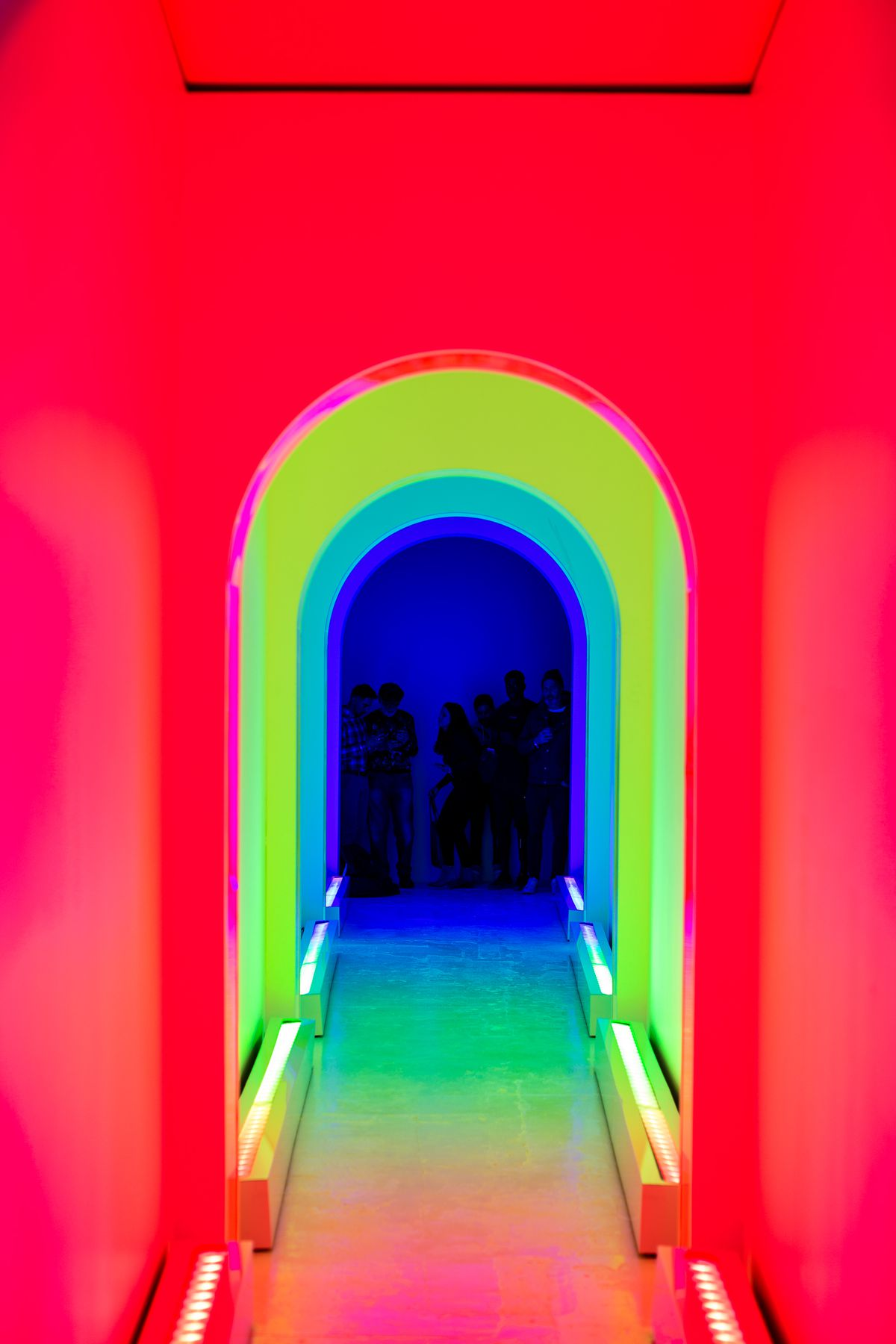 Dream Machine rainbow hallway lit up with different colors leading up to attendees taking pictures of the hallway