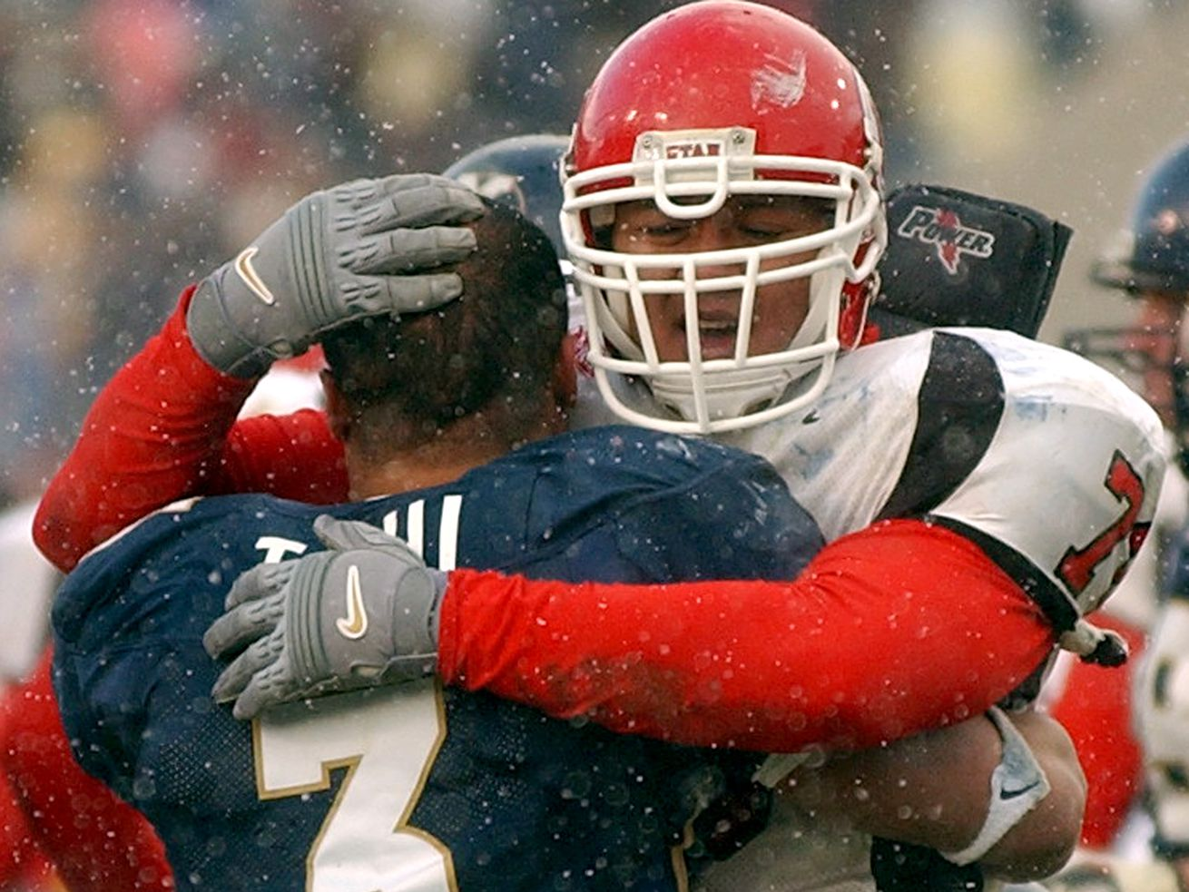 Utah's #78 Tavo Tupola hugs BYU's #3 Naufahu Tahi after the Utes defeated BYU 3-0 in Provo in 2003. The two programs would again be conference mates if a national writer gets his wish.