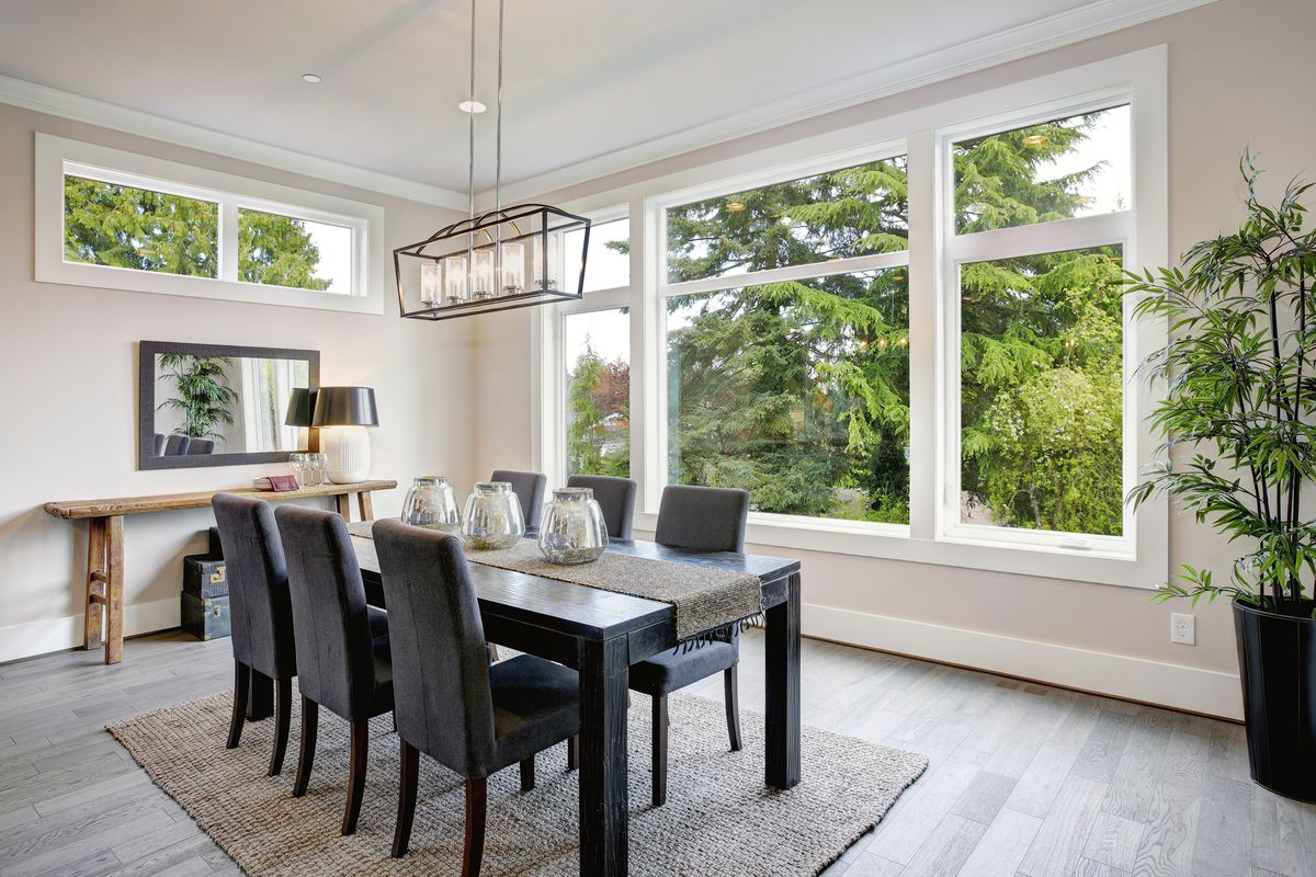 Dining room with big windows and a wall mirror.