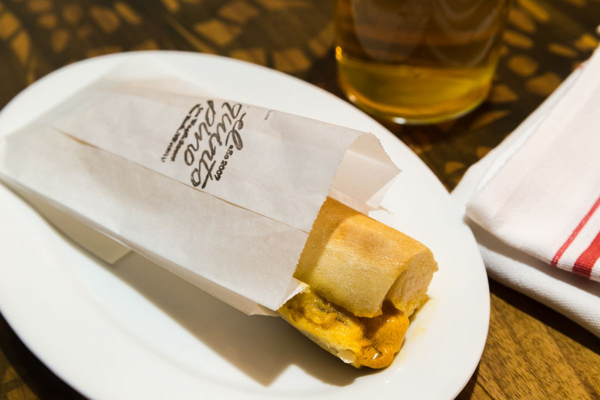 A baguette sandwich peeks out from a white sleeve, that's placed on a white plate. The sandwich features uni with a hint of mustard oil.