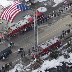 People watch as the funeral procession for Unified police officer Doug Barney goes through Holladay, where Barney served, before making its way to the Orem City Cemetery, where he will be laid to rest on Monday, Jan. 25, 2016. Barney was shot and killed in the line of duty by a man who seemingly had done nothing more than leave the scene of a traffic accident Sunday, Jan. 17, 2016.