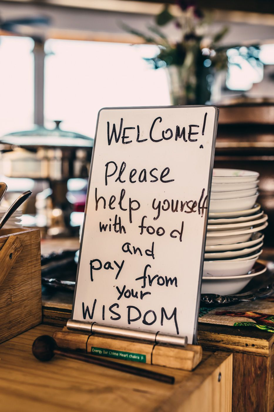 """A sign reads, """"Welcome! Please help yourself with food and pay from your wisdom."""""""