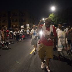 Aaron Jordan, 44, holds his fist in the air while walking with marchers on 83rd Street. | Colin Boyle/Chicago Sun-Times