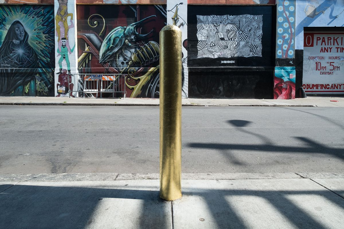 A gilded utility pole in the Mission, with murals and street art on nearby walls.