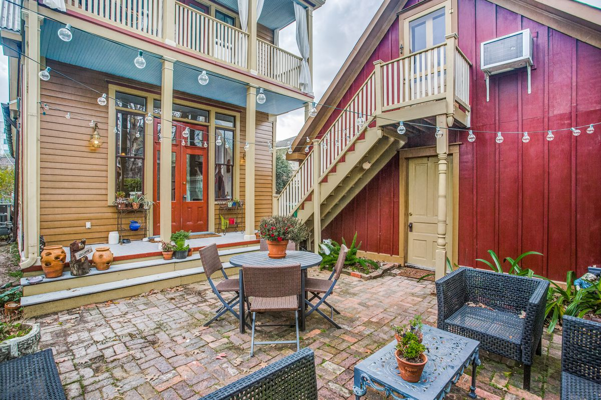 A backyard patio sits between the home and a red garage, with small seating and dining areas.