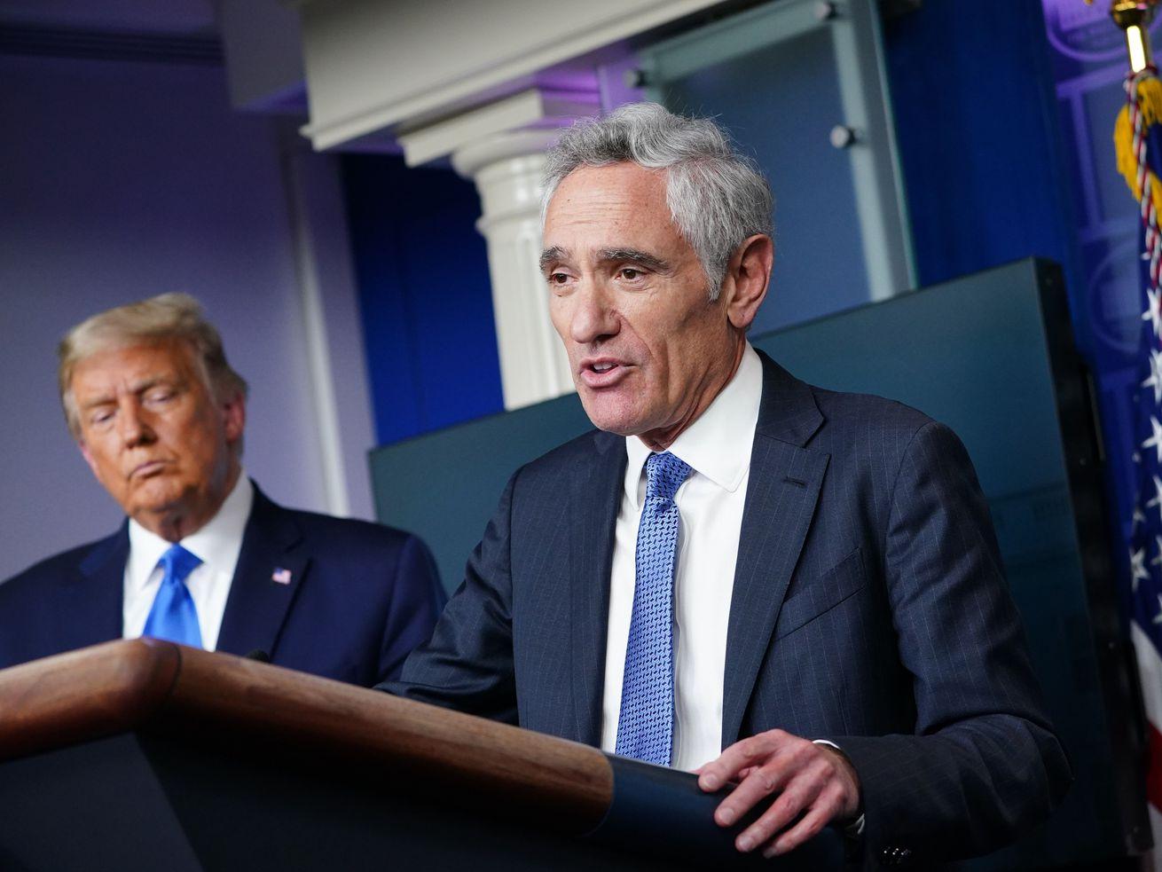 Le président américain Donald Trump écoute le conseiller en coronavirus de la Maison Blanche, Scott Atlas, s'exprimer depuis un podium lors d'une conférence de presse dans la salle de briefing Brady de la Maison Blanche le 23 septembre 2020, à Washington, DC.