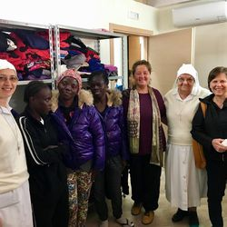 Sister Anita Herway, right, meets with refugees, nuns and a relief volunteer in a storage area where clothes, soap and other items are kept ready for distribution.