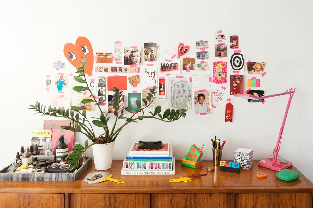 A wooden desk sits against a bedroom wall which is painted white. There are multiple pieces of decorated paper and artwork affixed to the wall with pink adhesive tape. There is a houseplant, books, and various office supplies on the desk.