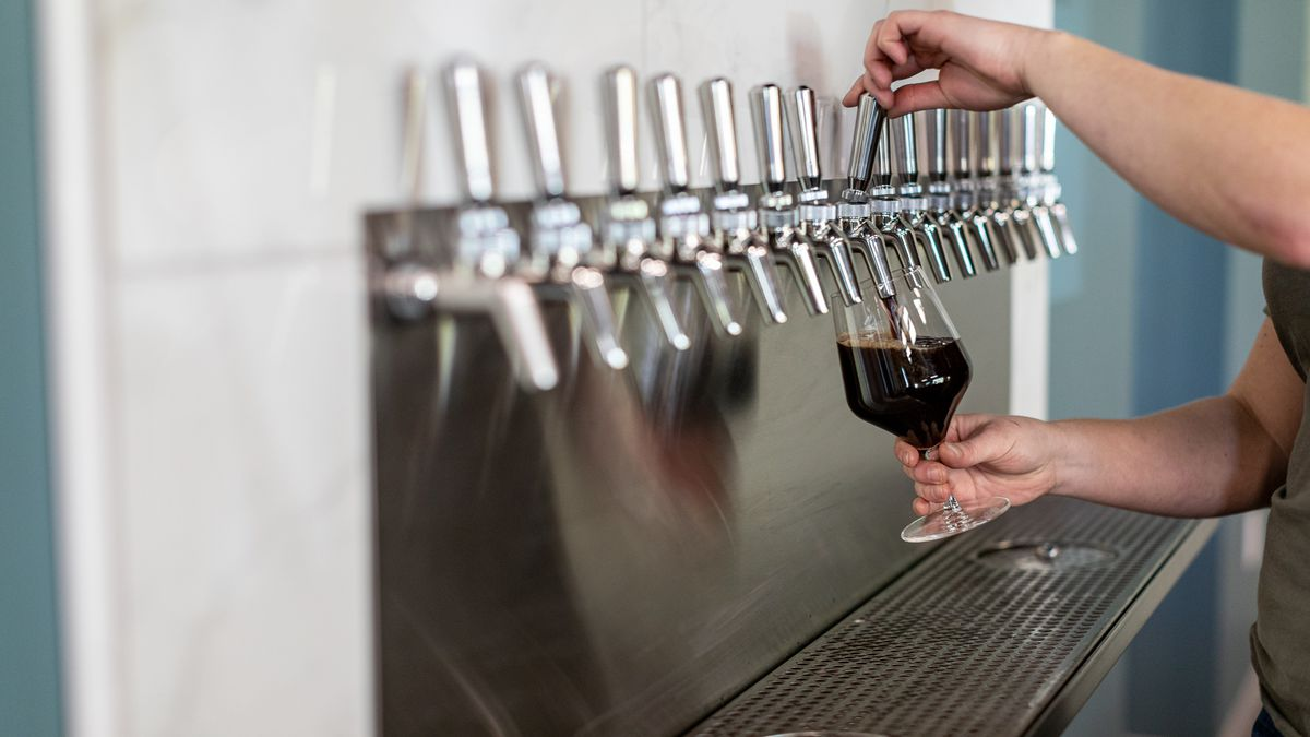 Rachel Szlaga's hands are shown pouring a dark coffee stout called Night Heron into a stemmed glass from a silver tap.