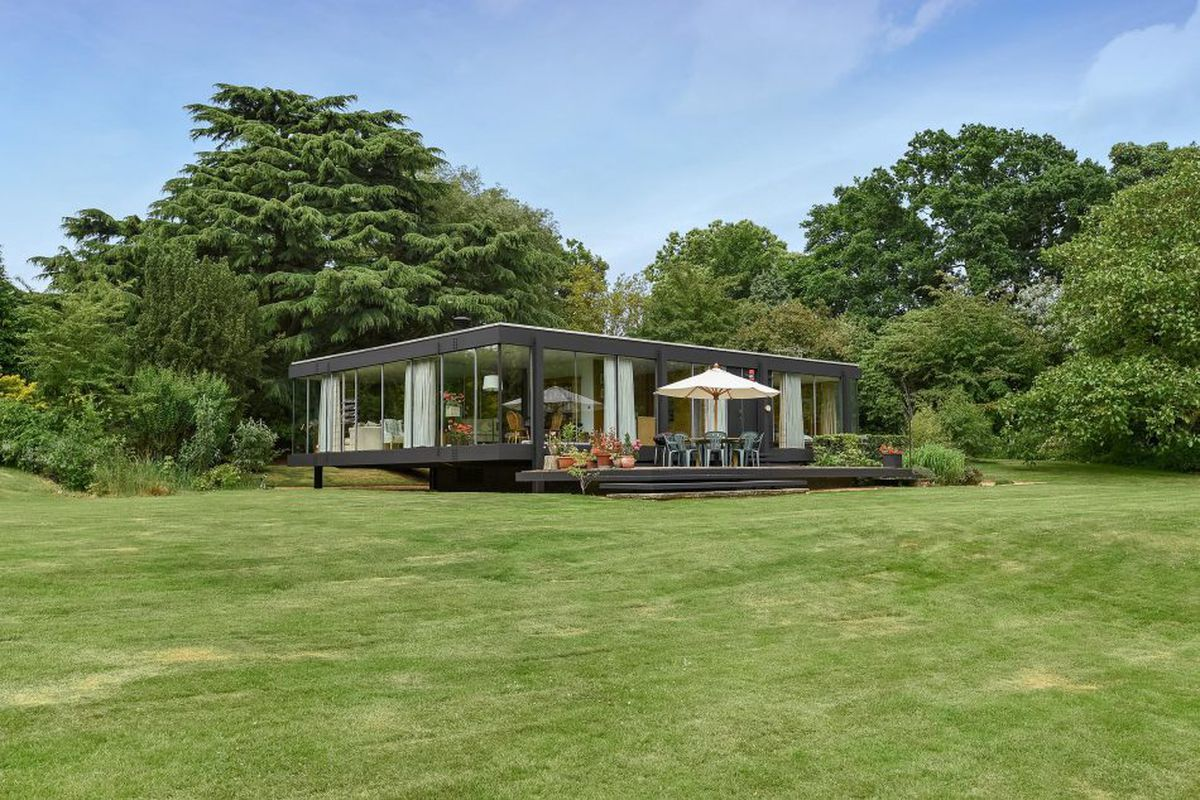 Exterior shot of flat cubic steel-framed house with wall of windows on short stilts amid landscaped lawn.