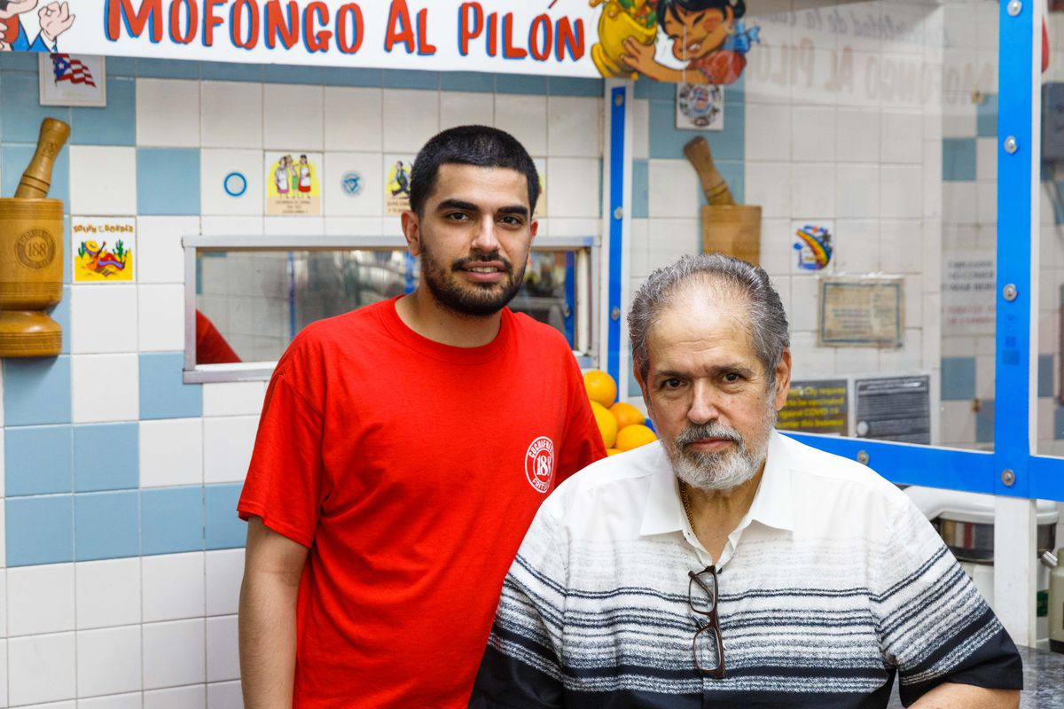 Manager Jay Coto stands in a red t-shirt next to his father, Jose Coto, at 188 Cuchifritos