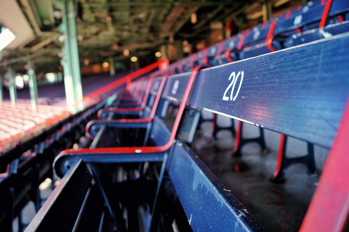 A row of wooden seats in an open-air ballpark.