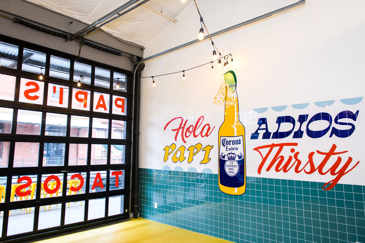 """A garage door at Papi Chulo's can open into the main dining space, which sits next to a wall mural of a Corona bottle with the words """"Hola Papi, adios thirsty."""""""