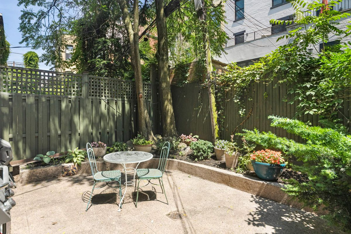 A patio with wood fencing, a round table with two chairs, several trees, and planters.