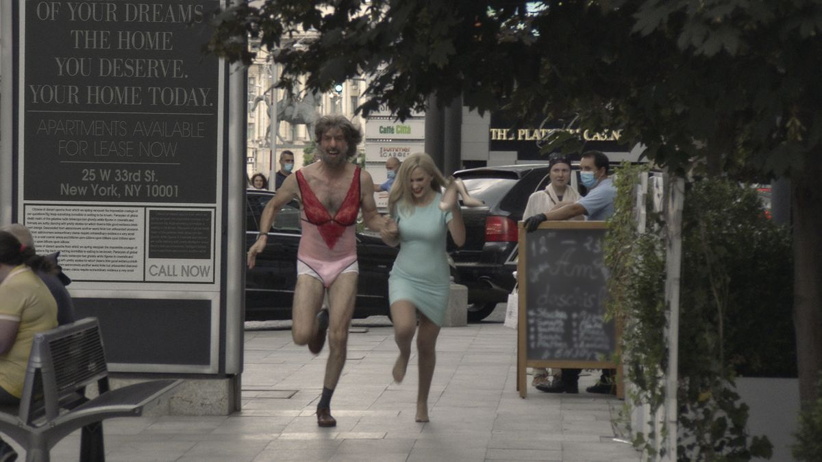Sacha Baron Cohen, in lingerie and a fake beard and wig, runs through the streets with Maria Bakalova in Borat Subsequent Moviefilm