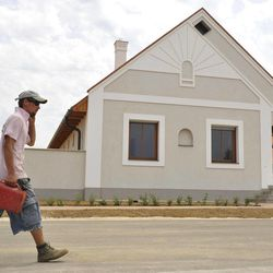 A man walks by at the state financed housing project for red sludge victims in the town of Devecser, Hungary, Thursday, July 14, 2011. The flood of toxic red sludge which devastated Devecser and the neighboring Kolontar in October has cost Hungary over 30 billion forints ($158 million, 111 million euro) in damages and reconstruction costs.