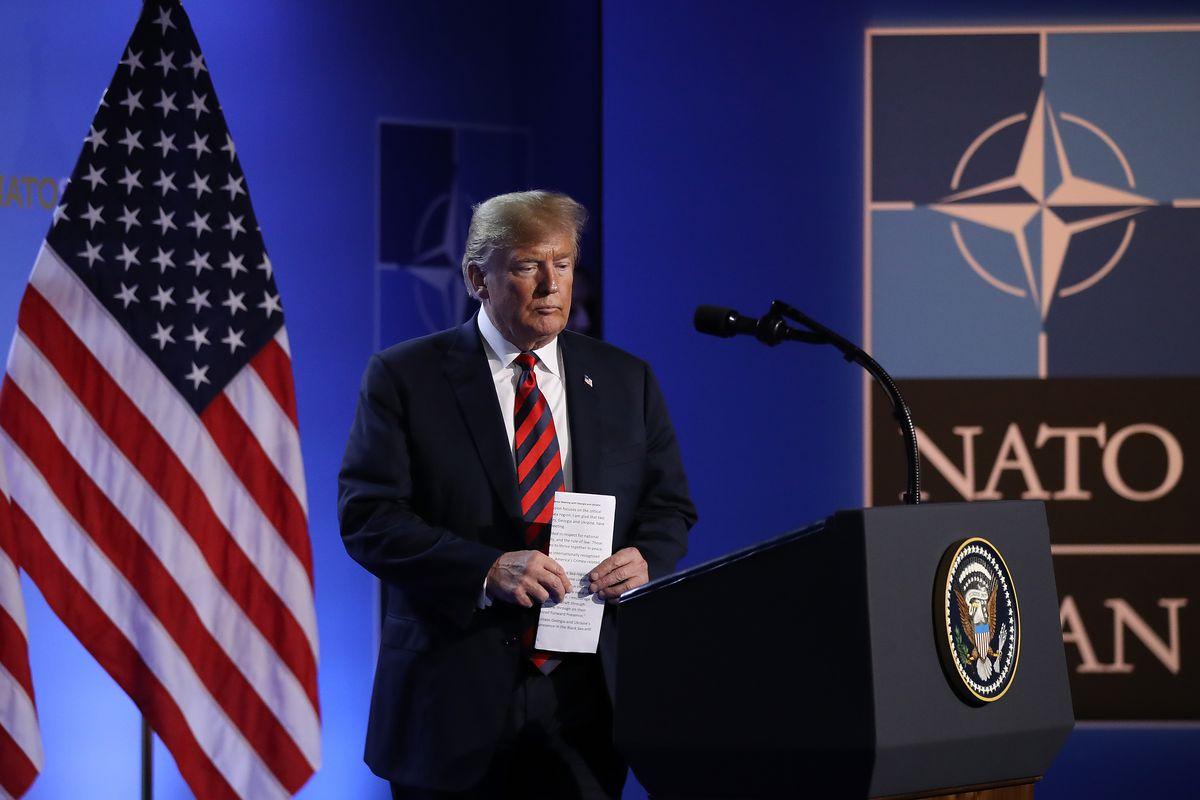 President Donald Trump walks toward a podium and microphone at a NATO summit.