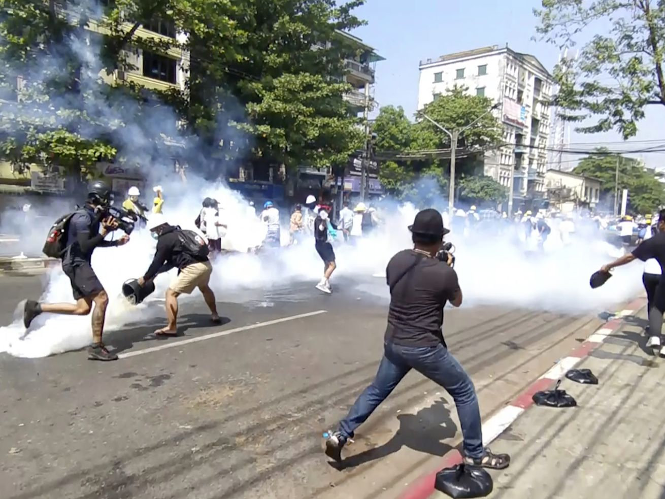 In this image from a video, anti-coup protesters run away from tear gas launched by security forces in Yangon, Myanmar Monday, March 1, 2021.