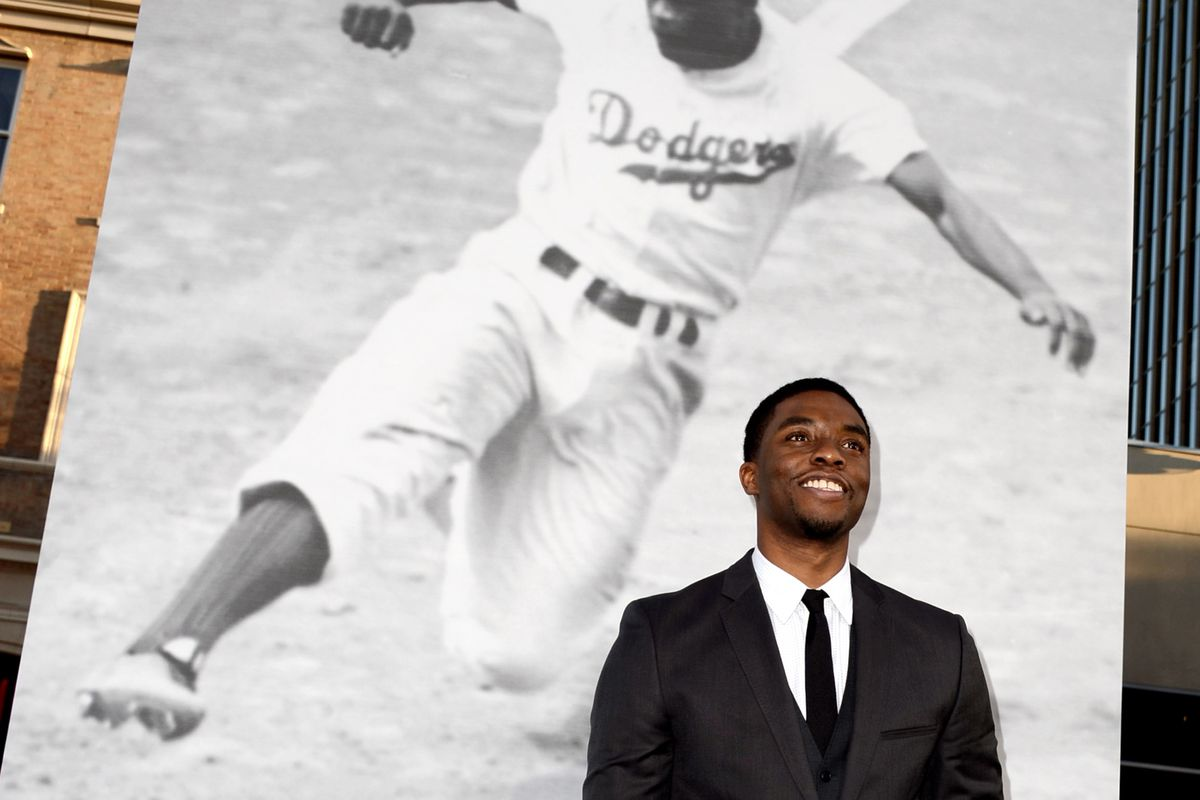 Chadwick Boseman stands in front of a poster of Jackie Robinson, who he played in the movie 42.