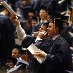 A couple students try to get the attention of family up in the audience prior to Spring Commencement Exercises at BYU Thursday, April 19, 2012 at the Marriott Center.