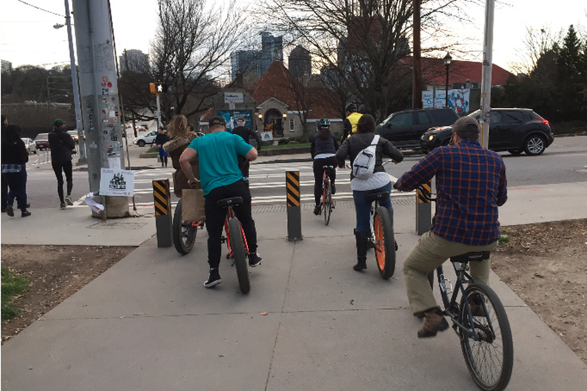 A photo of cyclists waiting for their turn at the intersection of 10th Street and Monroe Drive, a chokepoint for pedestrians.