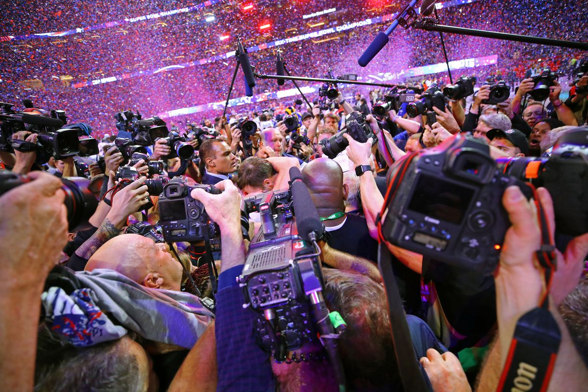Media members surround New England Patriots QB Tom Brady after defeating the Los Angeles Rams in Super Bowl LIII, Feb. 3, 2019.