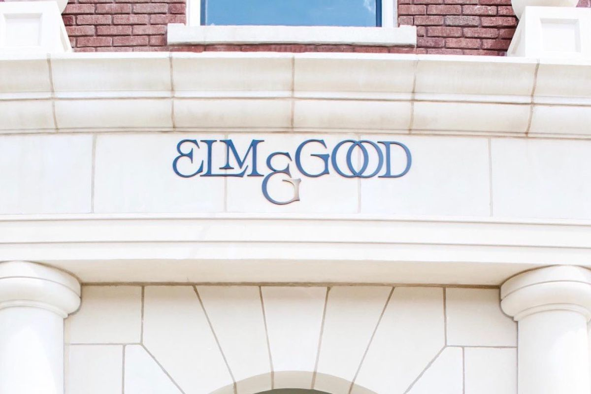 """Blue script sign reading """"Elm and Good"""" on a white marble building facade"""