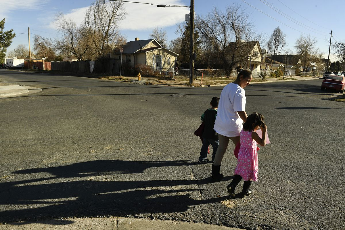 Olga Montellano walks with her daughter Milagros Santos, 3, right, and her neighor's son, Juan Pablo Ordoñez, 3, after preschool in their neighborhood.