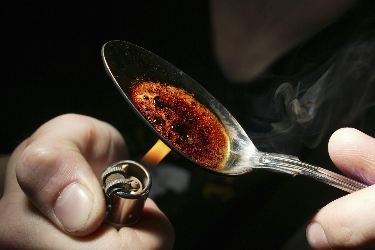 A person prepares heroin.