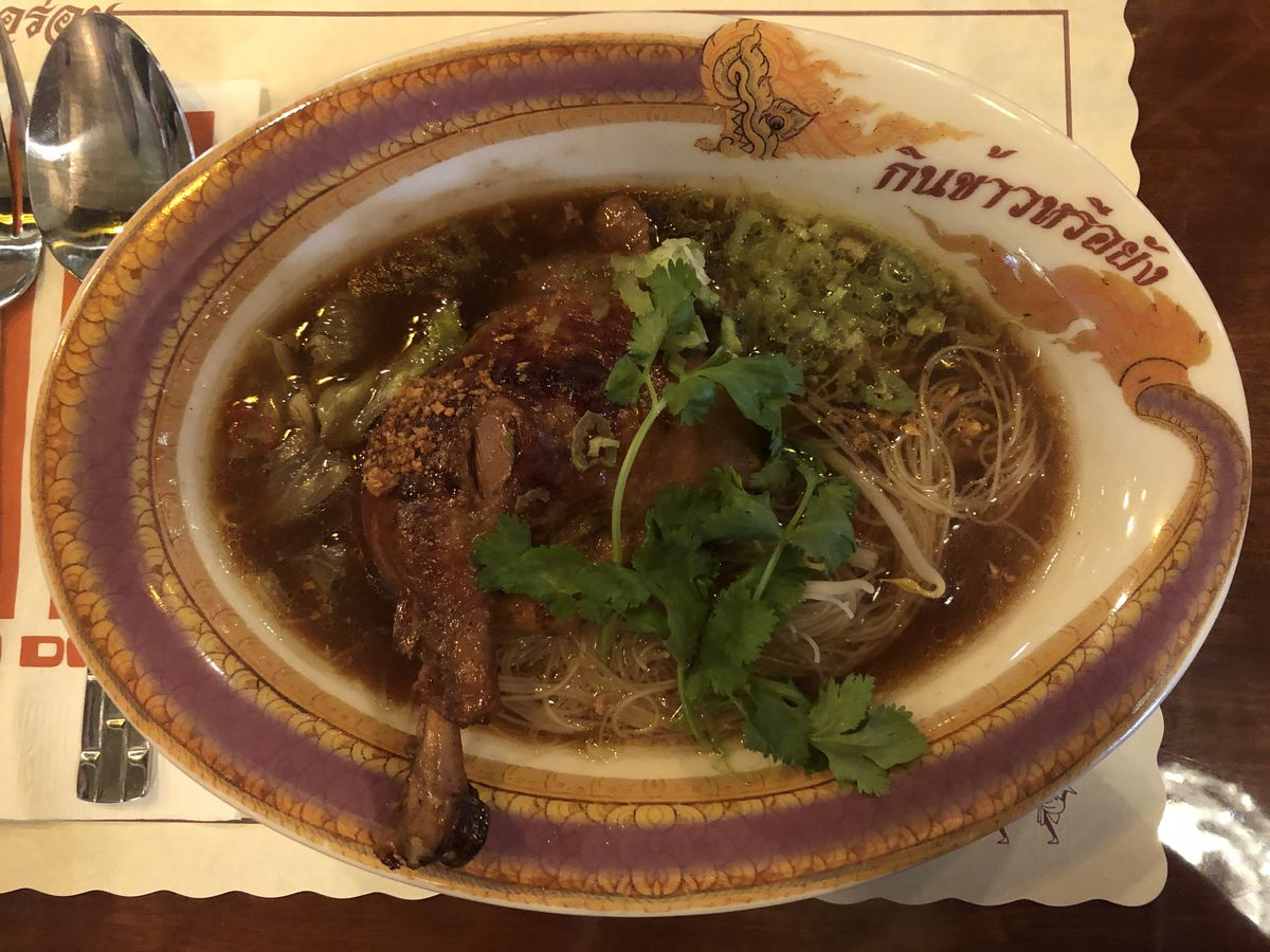 A bowl of soup with noodles and duck meat sitting on a table with a spoon off to the side