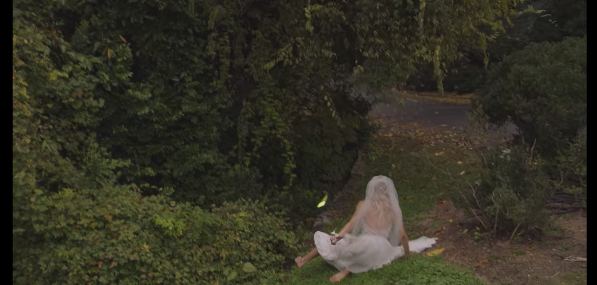 A woman in a wedding dress falls on the grass in a park.