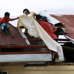 Residents repair a roof in Ormoc, Tuesday, Nov. 19, 2013.