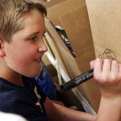 Benjamin Crane labels a box at the Utah Food Bank, where he volunteers with his family.