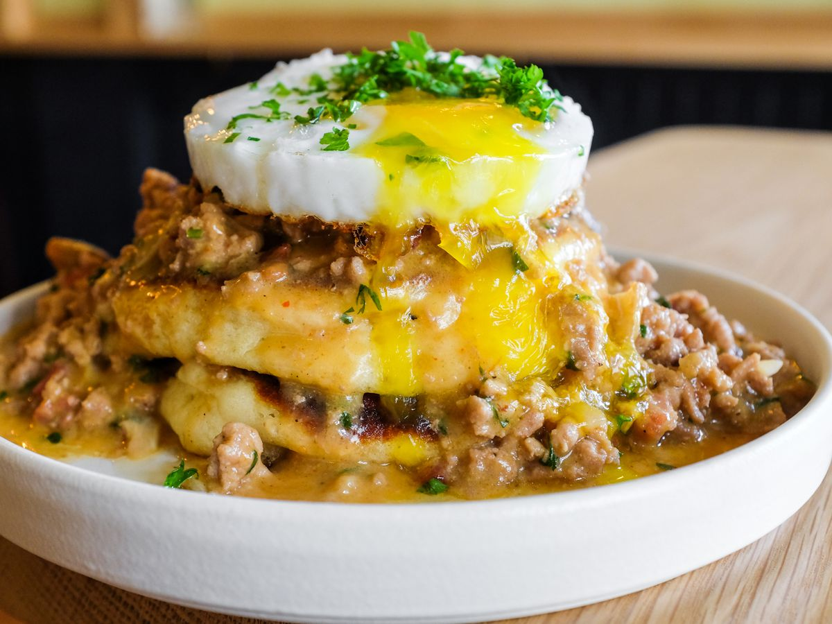A duck egg is perched on a stack of pancakes at Canard, drizzled with duck sausage gravy and chopped herbs.