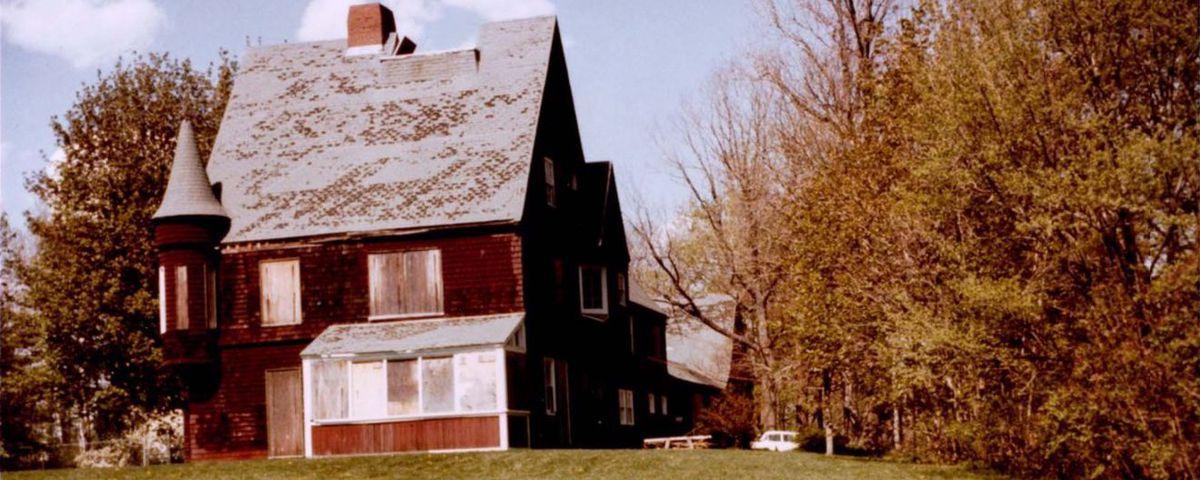 An old, barn-like house set amid a large field.