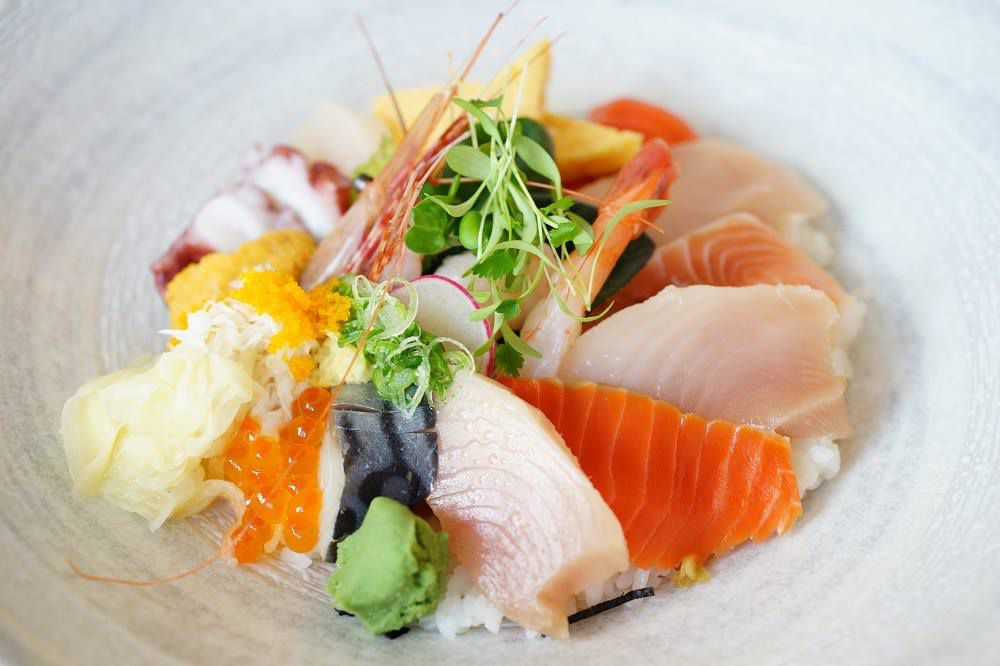A slate bowl of slices of sashimi in a mound