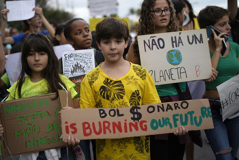 A boy takes part in a protest called by intellectuals and artists against the destruction of the Amazon rainforest, at Ipanema Beach in Rio de Janeiro, Brazil, on August 25, 2019.