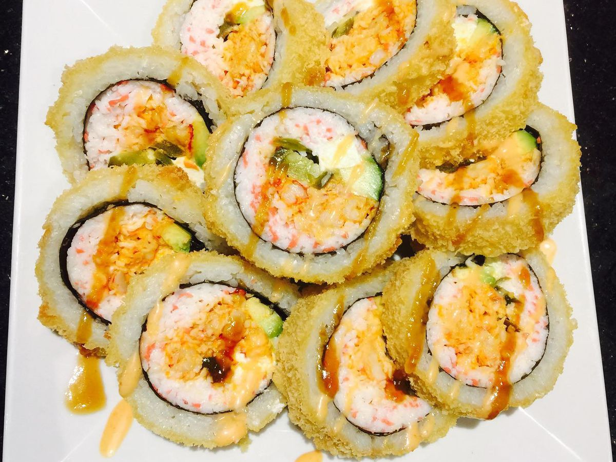 A sushi roll with cream cheese, salmon, cucumber, and sauce drizzled on top
