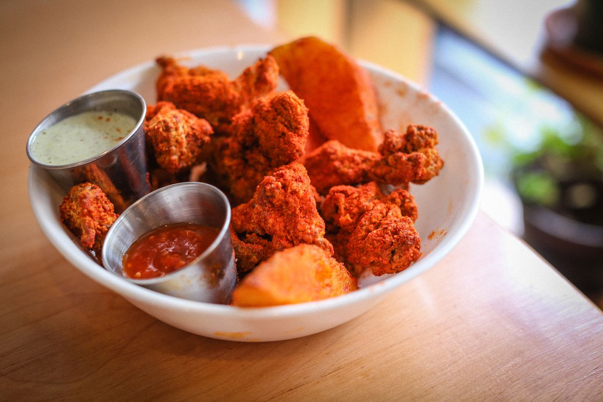 A white bowl containing orange spiced and fried chicken with two small metal containers of green and red dips sits on the edge of a light wooden table.