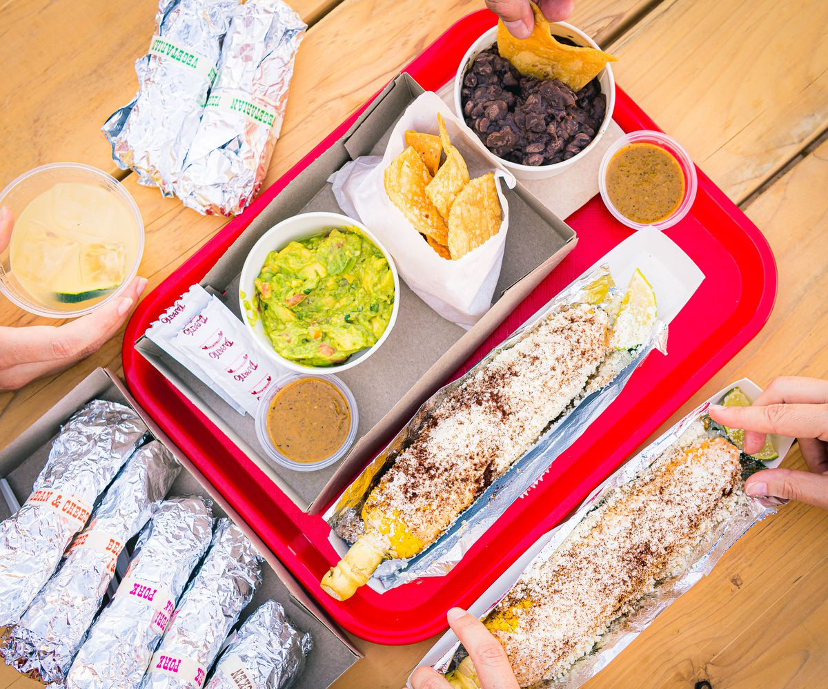 A red tray of tacos and queso and beans during daylight.