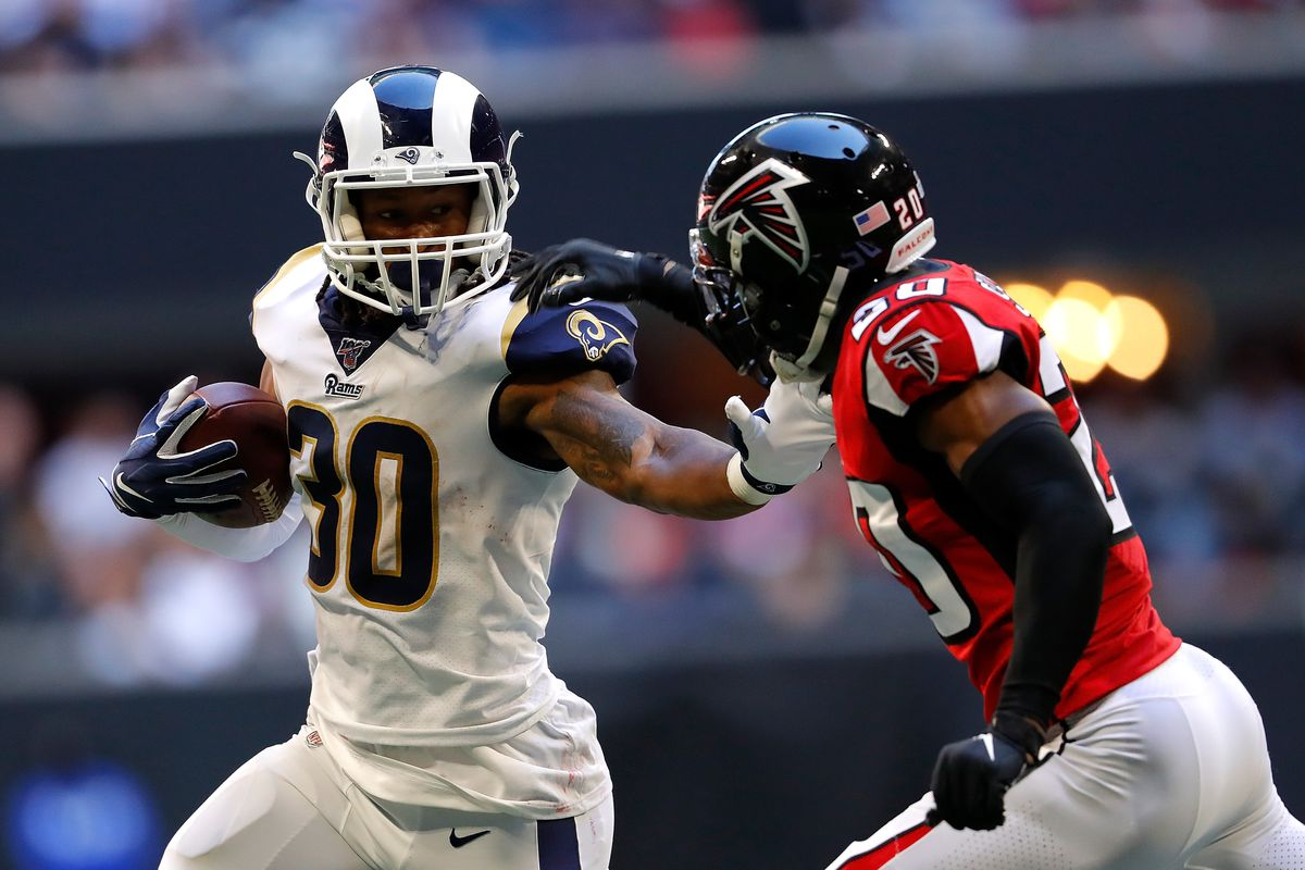 Todd Gurley II of the Los Angeles Rams rushes against Kendall Sheffield of the Atlanta Falcons in the second half at Mercedes-Benz Stadium on October 20, 2019 in Atlanta, Georgia.